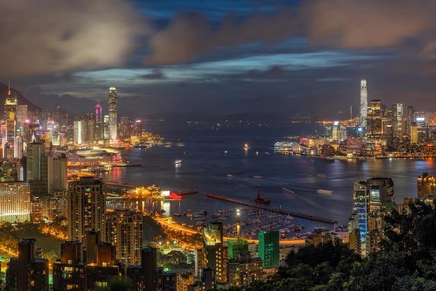 夕暮れ時の香港の街並みの超高層ビル、香港中部と九龍島、ビクトリアピークと港、冒険と旅行者のための赤い香炉山頂でのトレッキング