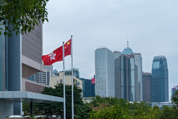 香港2016年1月29日:都市の高層ビルは香港の有名なランドマークです。香港の旗。香港は、世界で最も人口密度の高い地域の1つです。