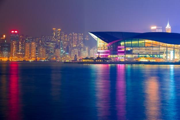 香港。島の堤防とコンベンション&エキシビションセンターの夜景と常夜灯
