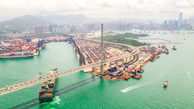 Hong kong port industrial district with cargo container ship and stonecutters bridge.