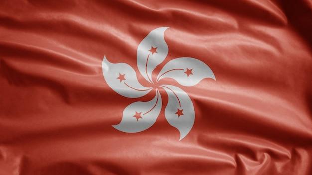 風になびく香港の旗。滑らかなシルクを吹く香港のバナーのクローズアップ