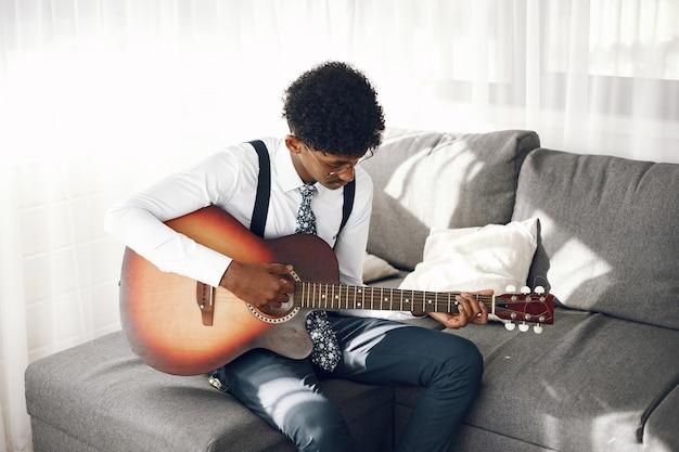 Hoobies 개념. 거실에 앉아 스타킹에 인도 젊은 남자. 기타를 연주하는 음악가.