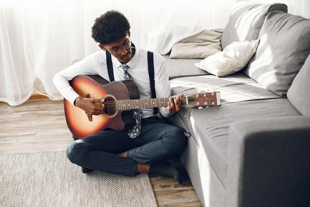 Концепция hoobies. индийский молодой человек в трико, сидя в гостиной. музыкант играет на гитаре.