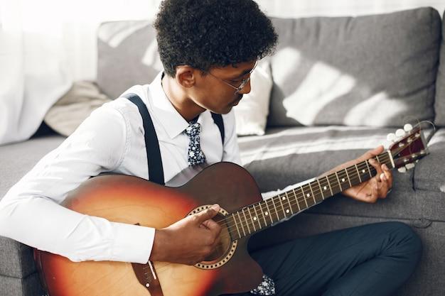 ホビーのコンセプト。リビング ルームに座っているタイツのインドの若い男。ギターを弾くミュージシャン。
