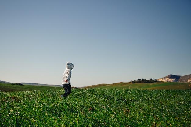 フード付きの子供が草の中を自由に走る