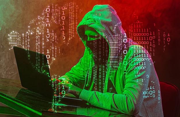 Компьютерный хакер с капюшоном крадет информацию с помощью ноутбука. понятие угрозы