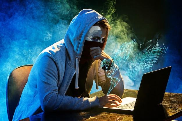 후드가 달린 컴퓨터 해커가 노트북으로 정보를 훔칩니다. 위협의 개념