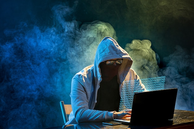 Hooded computer hacker stealing information with laptop. concept of threat
