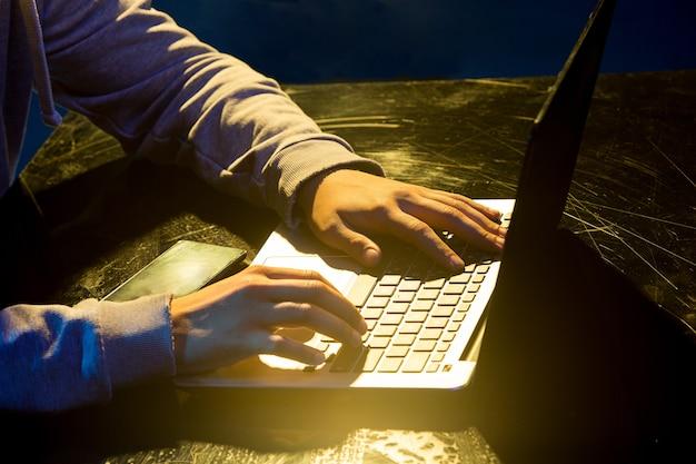 Компьютерный хакер в капюшоне крадет информацию с ноутбуком на цветном студийном фоне