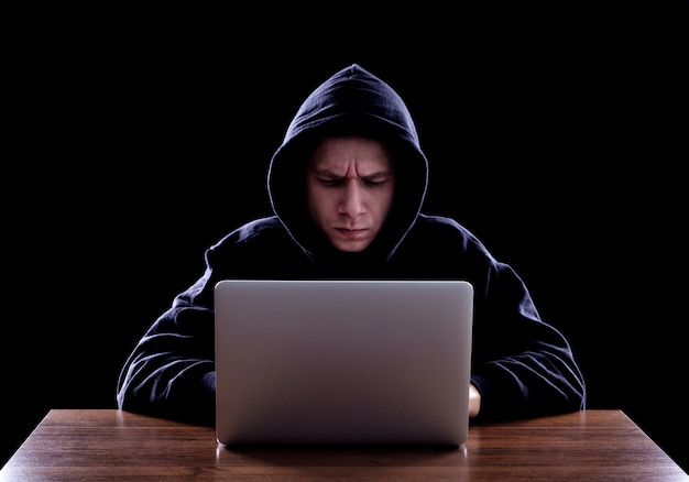Hooded computer hacker stealing information