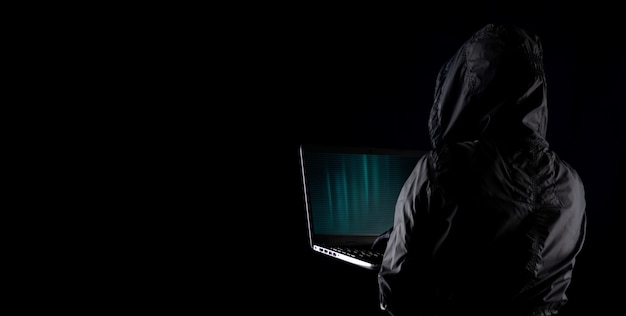 Hooded cybercriminal hacker using laptop to hack internet in cyberspace but black background, internet personal data security concept.