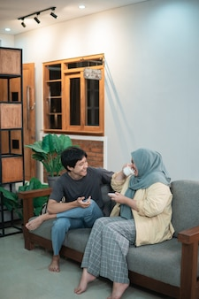 Hooded girl and an asian boy chat after coffee in the living room sitting on wooden chair