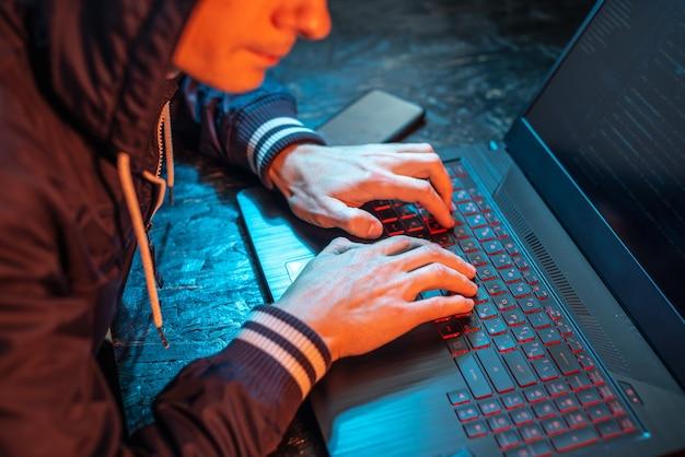 A hooded hacker is typing on a laptop keyboard in a dark room under a neon light