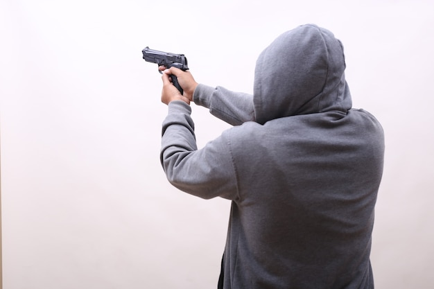 Hooded man holding gun isolated in white