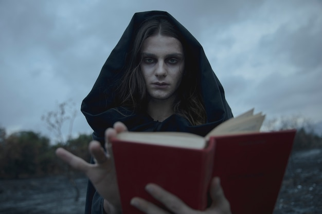 Hooded man looking at camera with blurred book