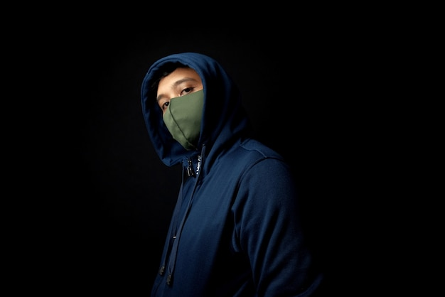 Hooded man stand in the dark