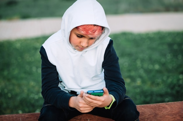 Hooded teenager looking at the mobile in a park