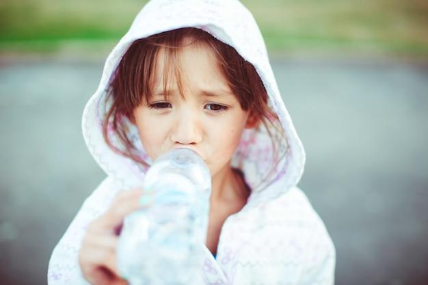 Маленькая девочка в белом hoody пьет воду