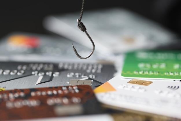 ローンと分割払いの概念へのテーブルの依存性に関するプラスチック銀行カードのフックとクレジット