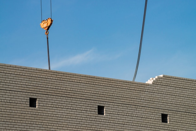 Hook of tower crane above unfinished building in construction site. background image of white brick wall under blue sky. background image of process building.