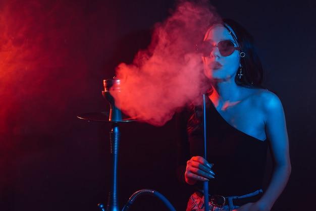 물담배 분위기. 그 소녀는 물담배를 피우는 것을 즐깁니다.