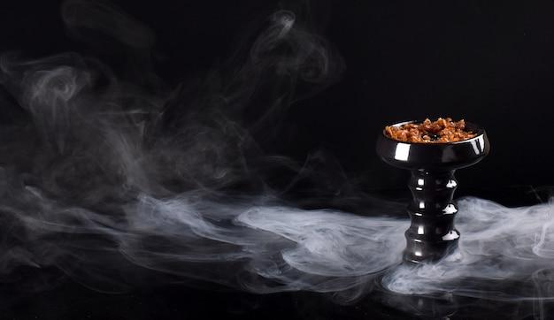 연기와 함께 검은 배경에 담배와 물 담뱃대 그릇
