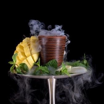망고 라임 민트와 검은 배경에 담배와 물 담뱃대 그릇