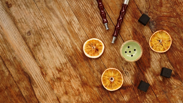 Hookah bowl on wooden background with dry oranges, coal and hookah pipes