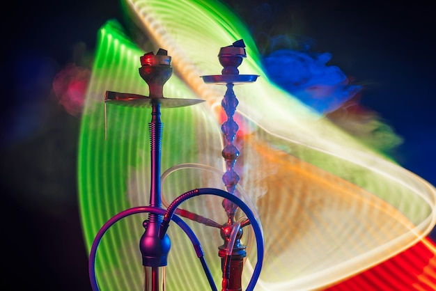 Hookah bowls with coals in smoke with colorful neon bright lights