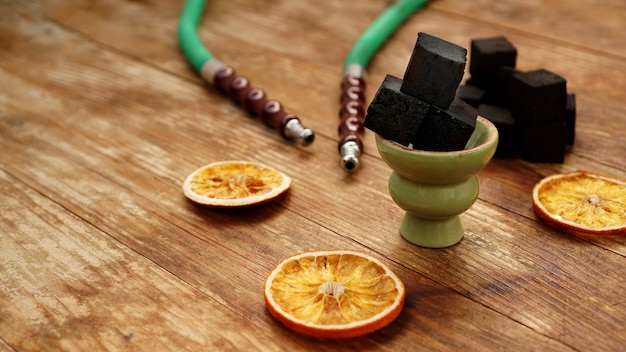 Hookah, charcoal, dry orange slices and christmas red balls on a wooden table