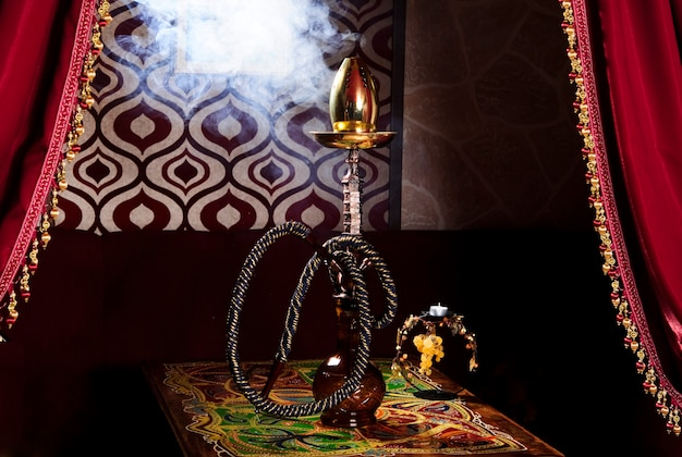 Hookah on a dark background of a blurry bar with a bokeh.copy space