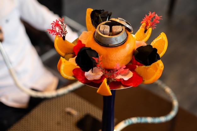 オレンジ、黒いバラなどの花で飾られた水ギセル