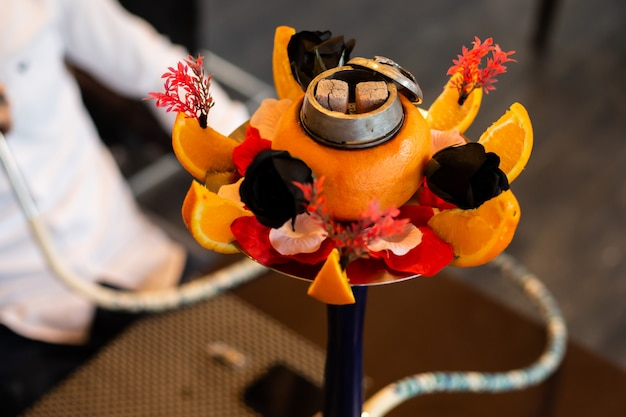 Hookah decorated with orange, black roses and other flowers