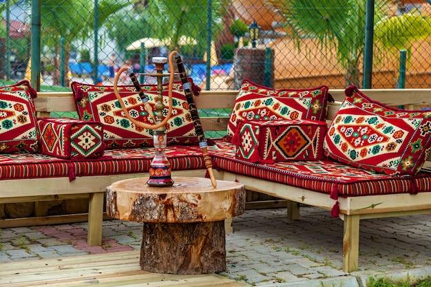 나무 테이블에 물담배와 소파에 밝은 다색 베개, 터키 물담배