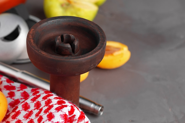 Hookah pipe and shaft with fruits on gray background, close up