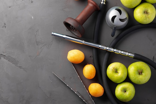 Hookah pipe and shaft with fruits on gray, close up