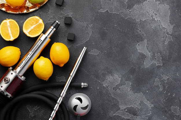 Hookah pipe and shaft with fruits on gray wall, close up