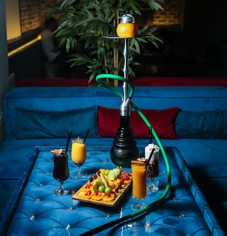 Hookah with mixed fruits on the wooden board and cocktails side view