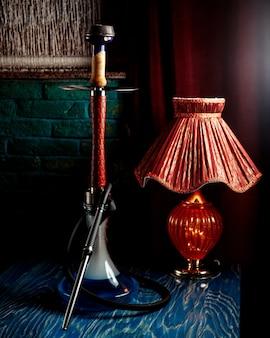Un narghilè con lampada rossa