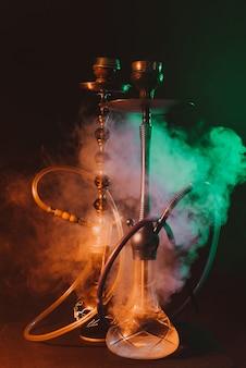 Hookahs on a smoky dark room with neon lighting and smoke