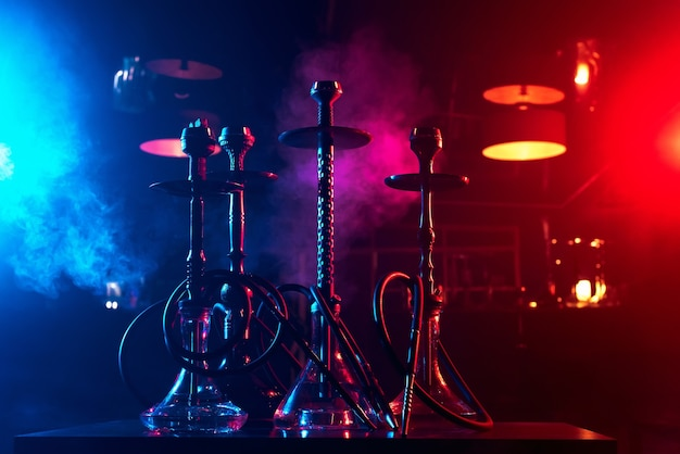 Hookahs on the table with smoke and red and blue light in the lounge cafe. concept of traditional eastern arabic relaxing with a shisha