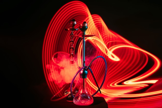 Hookahs with hookah coals with a cloud of smoke with red neon lighting