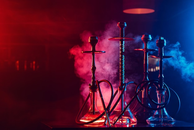 Hookahs with shisha coals in bowls against a background of smoke with neon lighting in a restaurant with a copy space
