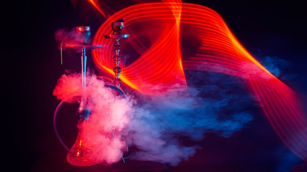 赤と青のネオンライトが付いているテーブルの上のボウルのシーシャ石炭と水ギセル