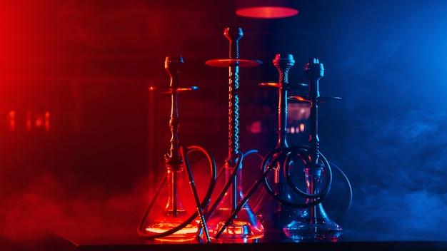 Кальяны с кальянными стеклянными колбами и металлическими чашами с углями для релаксации с потреблением табачного дыма в ресторане с копией пространства