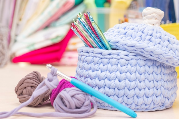 Крючки в вязаной корзине из трикотажной пряжи. рядом с ним шарики пряжи на столе. хобби и вязание.