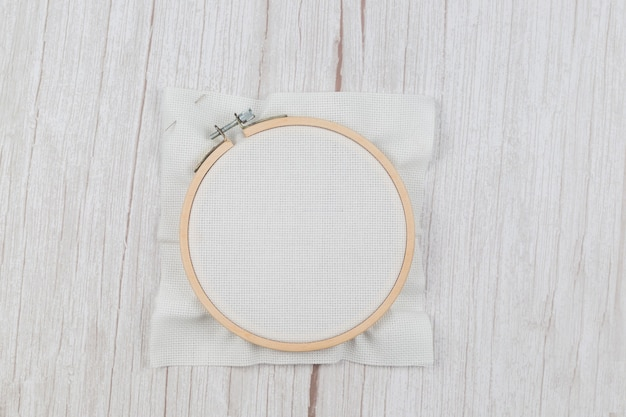 Hoop for cross stitch with stretched canvas, blank for the designer, on a wooden background