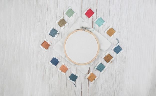 木製の背景に、ストレッチキャンバス、デザイナーのための空白のクロスステッチのフープ