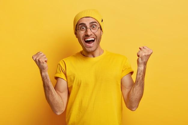Ура! слишком эмоциональный счастливый человек заставляет кулаками качать от успеха и счастья, приветствует достижение цели
