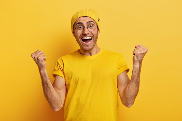Hooray! overemotive happy man makes fist pump from success and happiness, cheers achieving goal